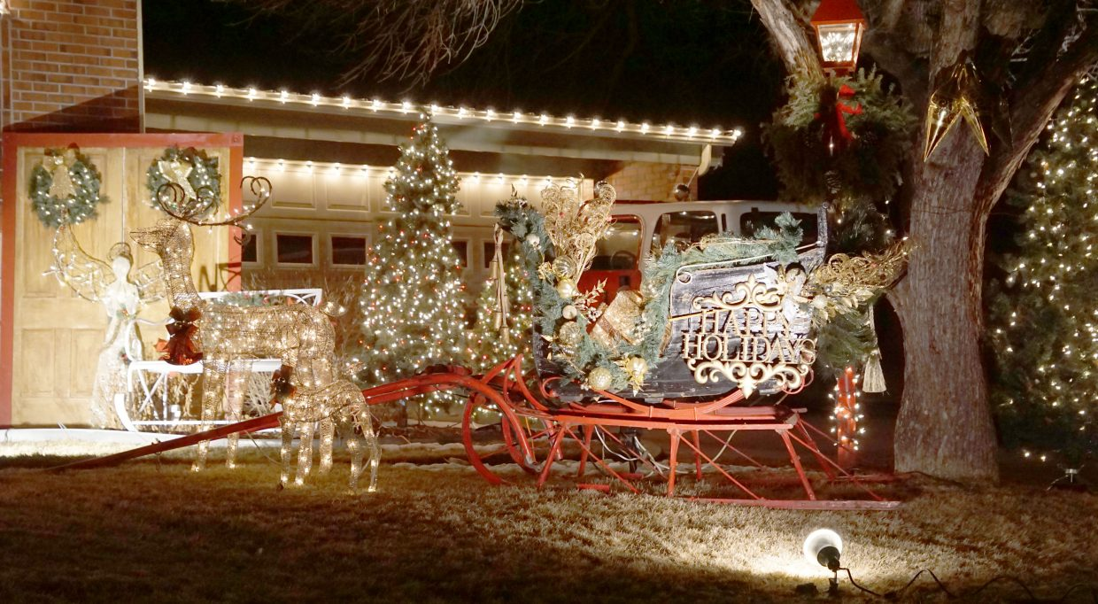 Old world charm and details, such as this antique sleigh, are part of the winning light display at the Bird residence.