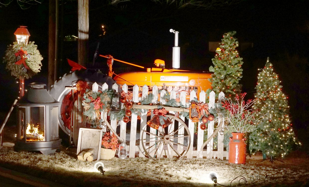 A wood fire burns next to a festive tractor as part of the holiday display at the Bird residence in Craig.