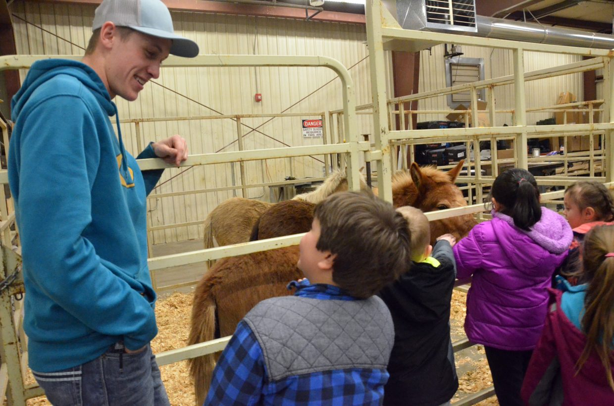 Kasen Brennise chats with Sandrock Elementary School students during Barnyard Day hosted by Moffat County High School Future Farmers of America.