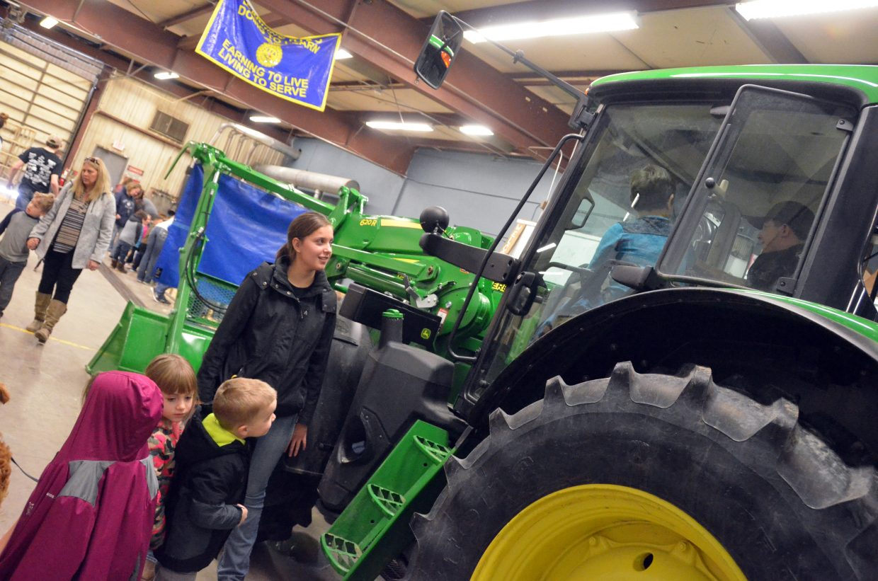 Tauren Farquharson helps Sandrock Elementary School students wait for their turn in behind the wheel of a tractor during Barnyard Day hosted by Moffat County High School Future Farmers of America.