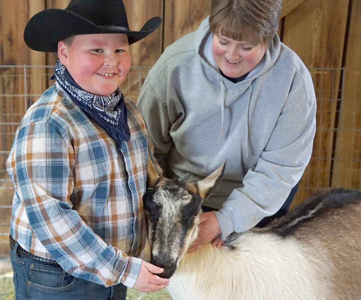 Parents Doug and Chrissy Winters wanted to raise their sons on a family farm and in 2011 there were able to buy their dream property in Moffat County. Now the family works together to raise farm animals such as chickens, cattle, pigs, and rabbits along with their dairy goats. Pictured here Chrissy Winters helps 8-year-old Zach with one of the goats.