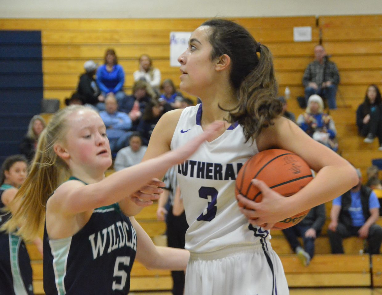 Lutheran's Isabel Dycus holds onto the ball and swats away a steal attempt by The Academy's Jenna Beagle late in the Round of 32 at Moffat County High School. The Lutheran Lions beat the Wildcats 56-39 and will face Moffat County Saturday in the Sweet 16.
