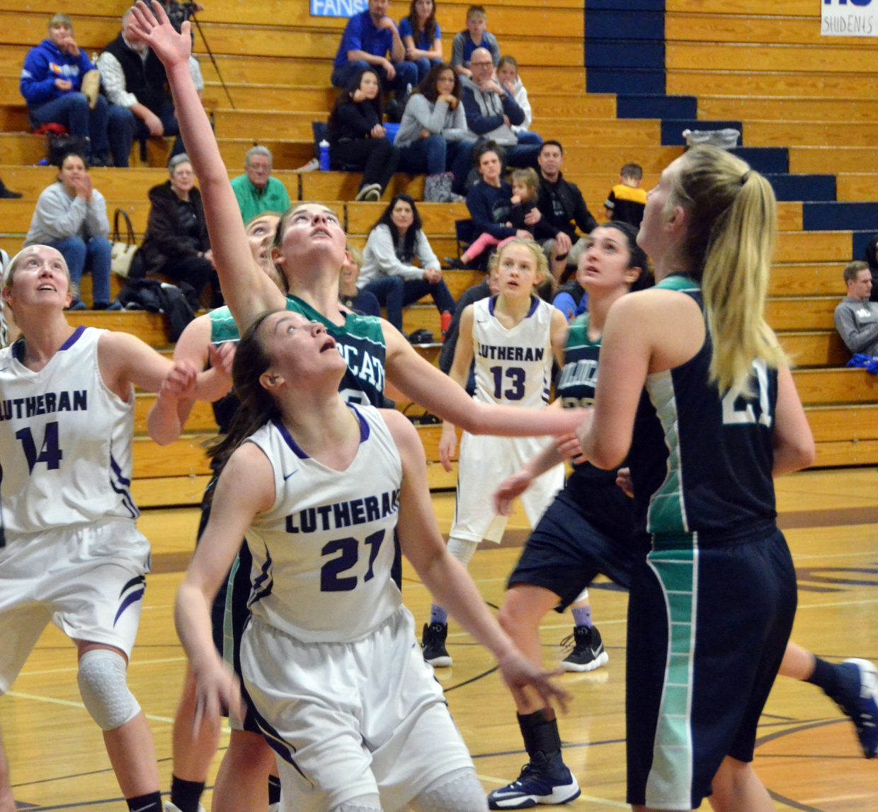 Players with Lutheran and The Academy cluster beneath the basket for a rebound in the Round of 32 at Moffat County High School.