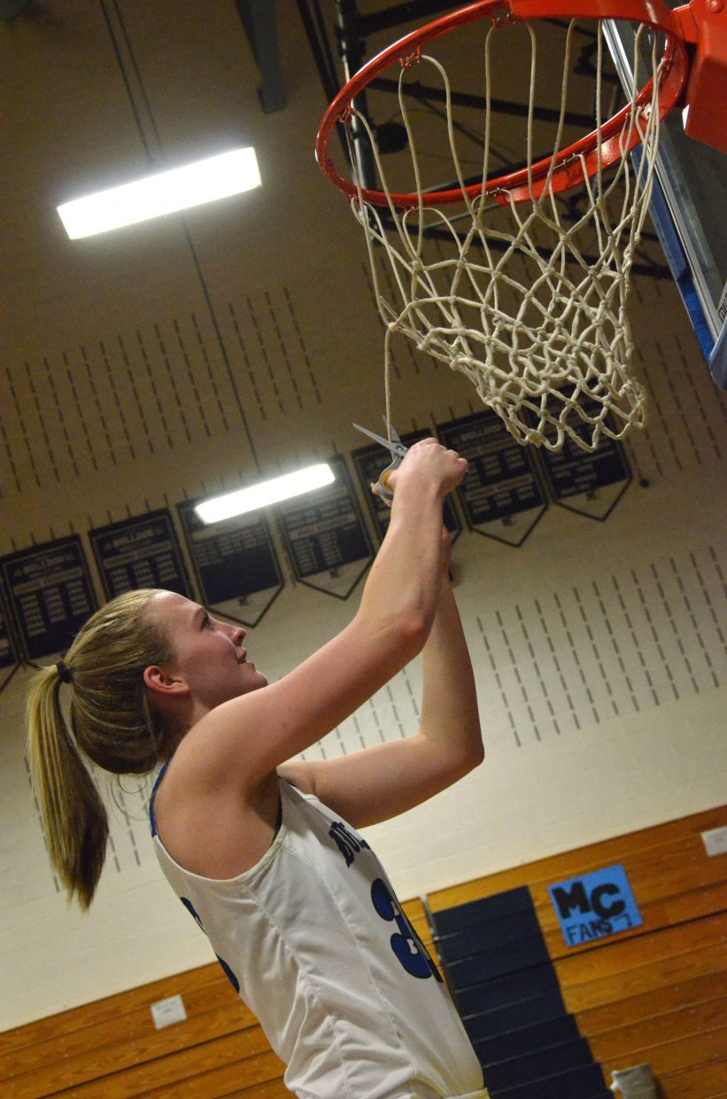 Moffat County High School's Jana Camilletti cuts loose a piece of the home net in the MCHS gym following a regional tournament win against Lutheran.