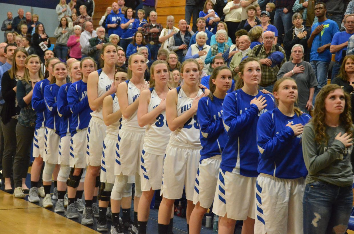 Moffat County High School players, coaches and managers stand for the national anthem.