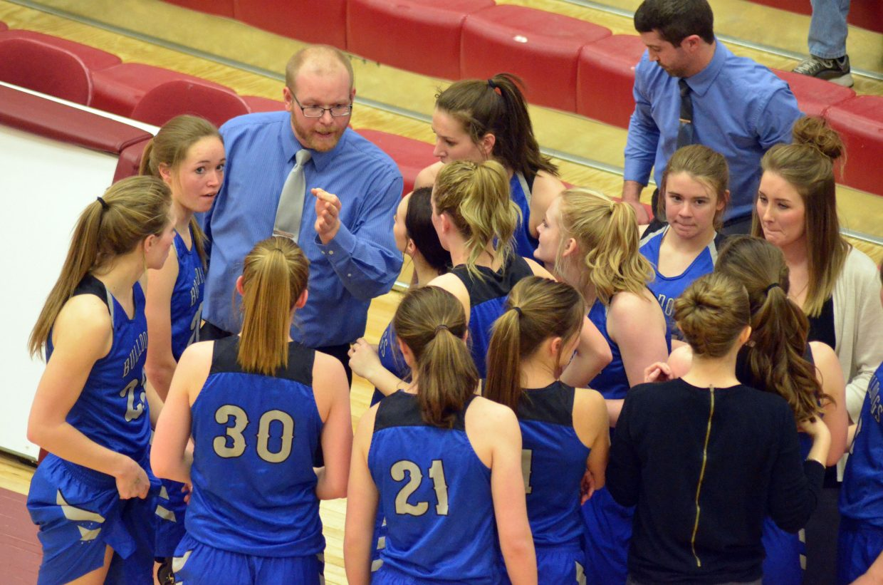 Moffat County High School girls basketball players heed the advice of coach Kenley Nebeker before heading back out for the second half against Kent Denver.