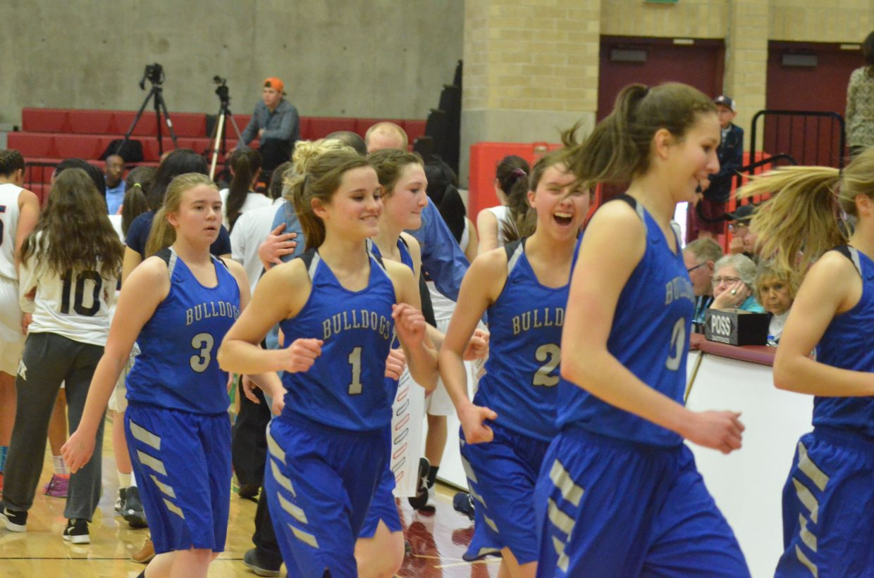 The Moffat County High School girls basketball team heads off the court with gusto after a 44-32 win over Kent Denver.