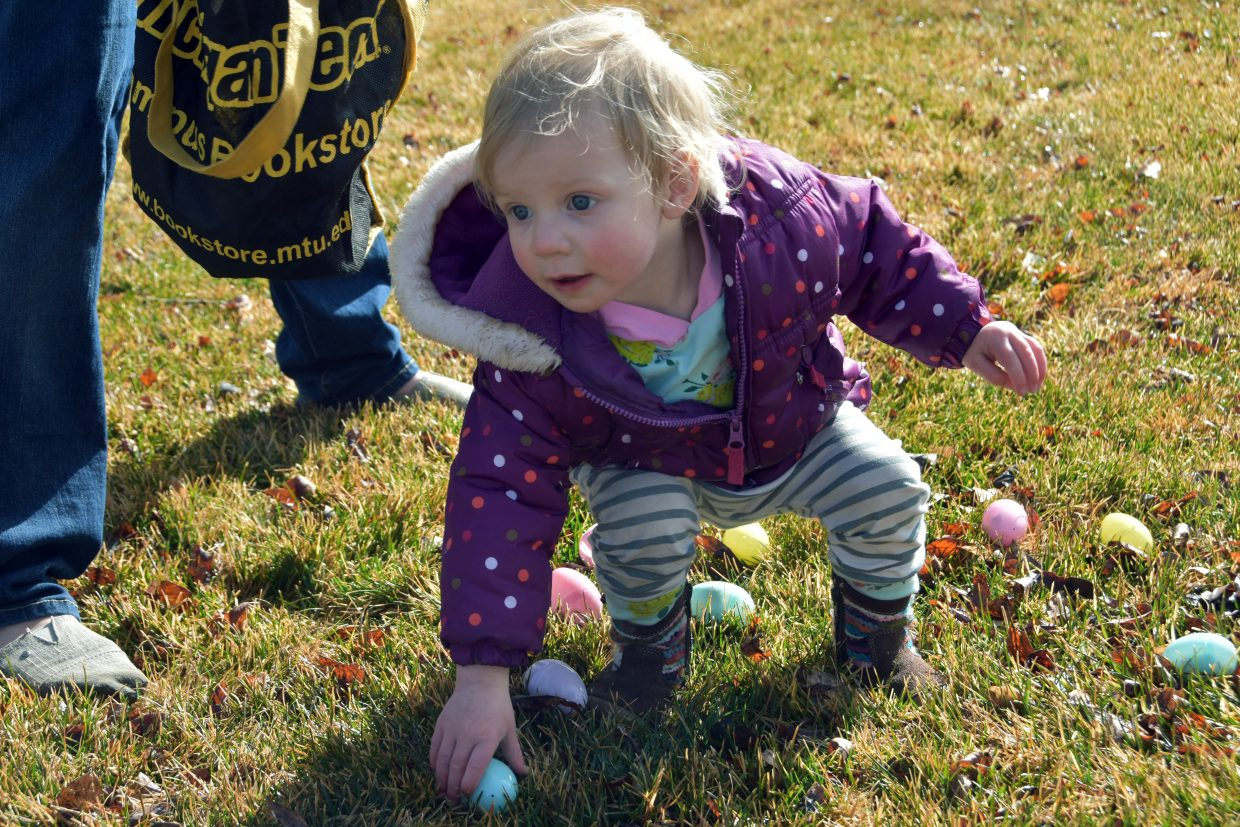 Ainsley Fraher, age 2, picks up a plastic egg at the State Farm Easter Egg Hunt.