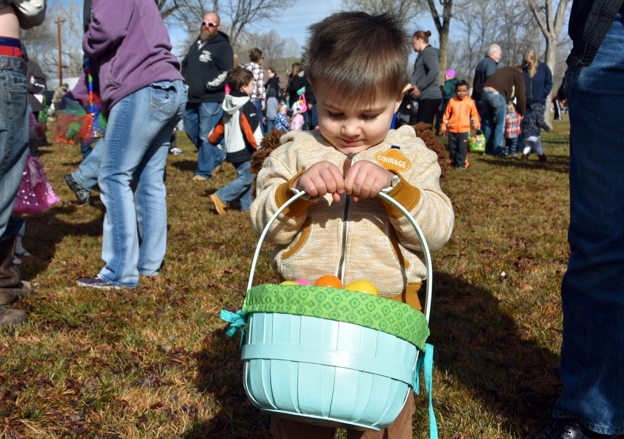 Alex Albaugh, 2, shows off his prizes at the State Farm Easter Egg Hunt.