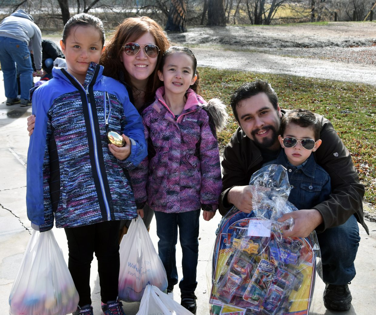 From left, Mia Valenzuela, age 6; Erika Valenzuela and Valeria Valenzuela, age 5; and Joe Romero and Rogelio Romero-Valenzuela, age 2,  pose with Rogelio's prize basket. Rogelio found the golden egg hidden for children in the 0-3 year old age division.