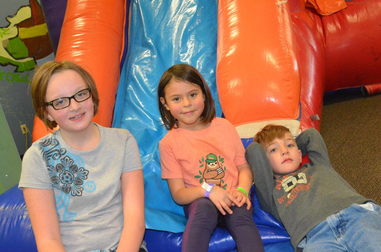 From left, Gracie Burks, 10, Annabelle Mackey, 6, and Christopher Merwin, 6,  take a break from bouncing at Adventure Zone following Saturday's Easter egg hunt.