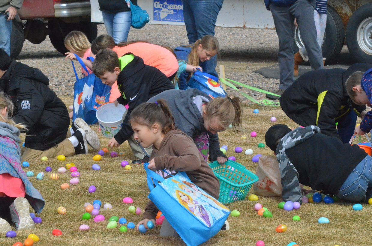 Kids grab as many eggs as their baskets and bags can hold at Saturday's Easter egg hunt at New Creation Church.