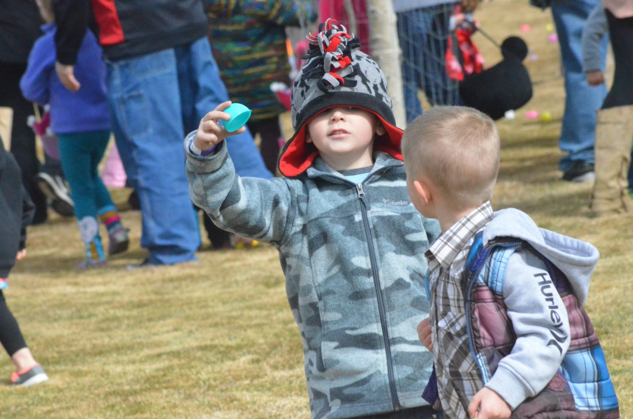 Young hunters examine an empty plastic egg during New Creation Church's Easter egg hunt.