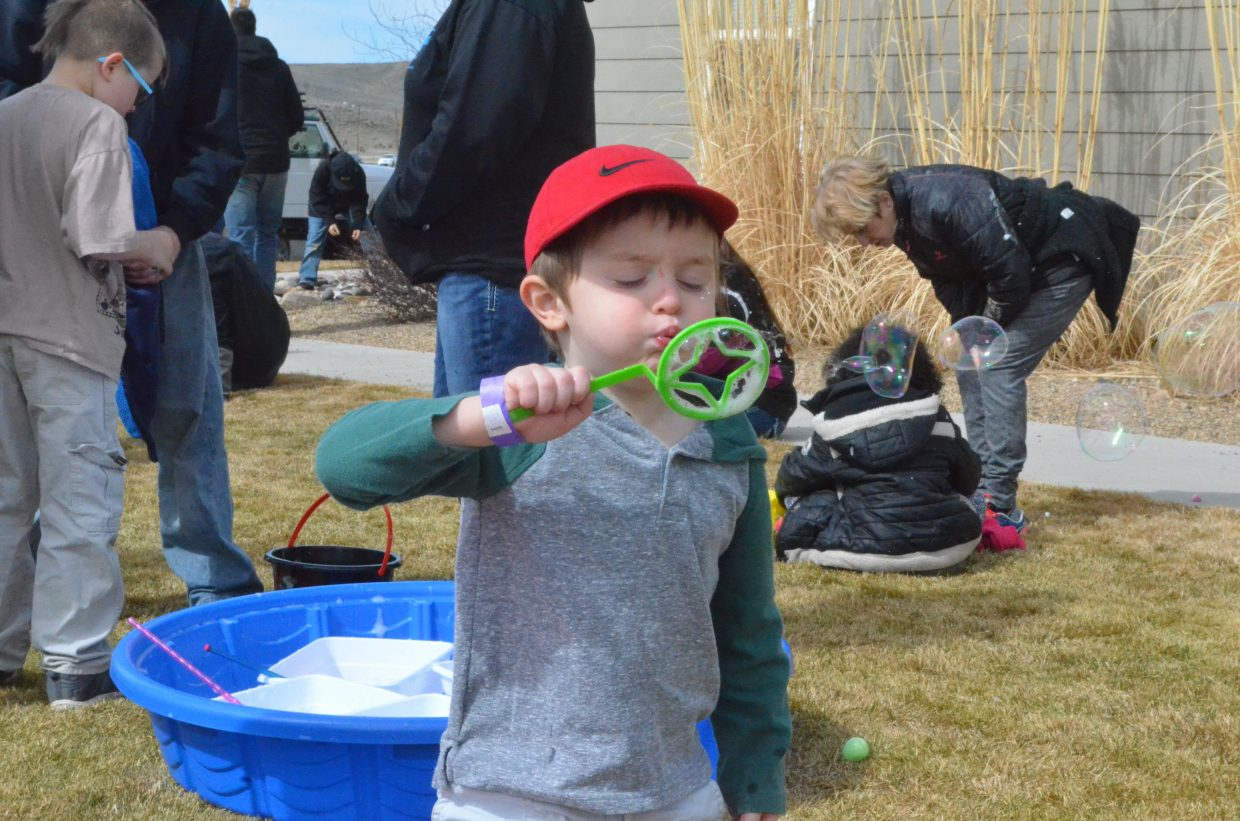 Braylen Curtis, 3, blows bubbles during New Creation Church's Easter egg hunt.
