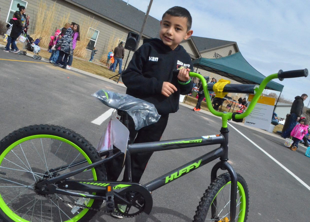 Evan Balbuena smiles with his new Huffy bicycle, won during  New Creation Church's Easter egg hunt.