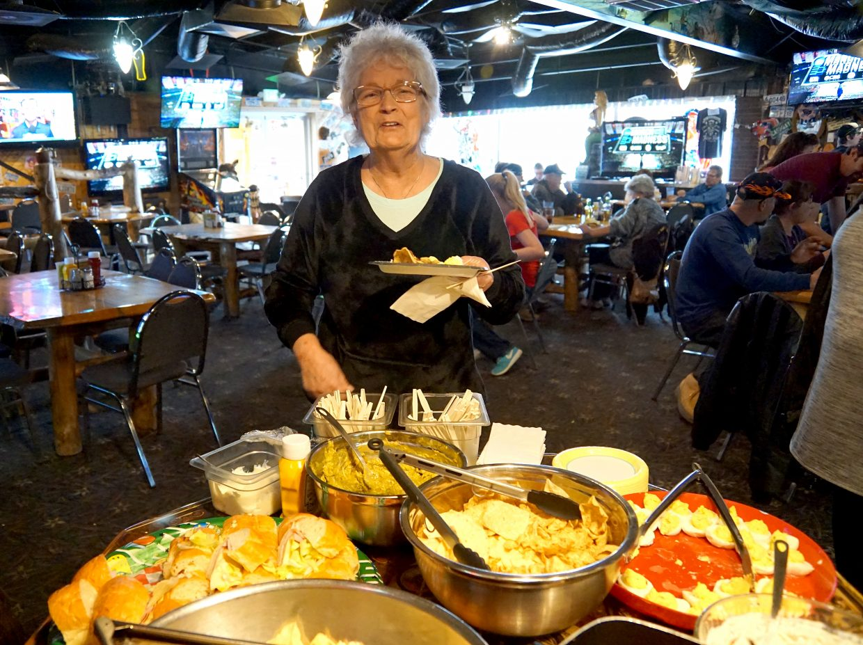 Ann Kidder, better known as Mrs. Claus to many, prepares herself a plate during a going away party held to honor her and her husband.