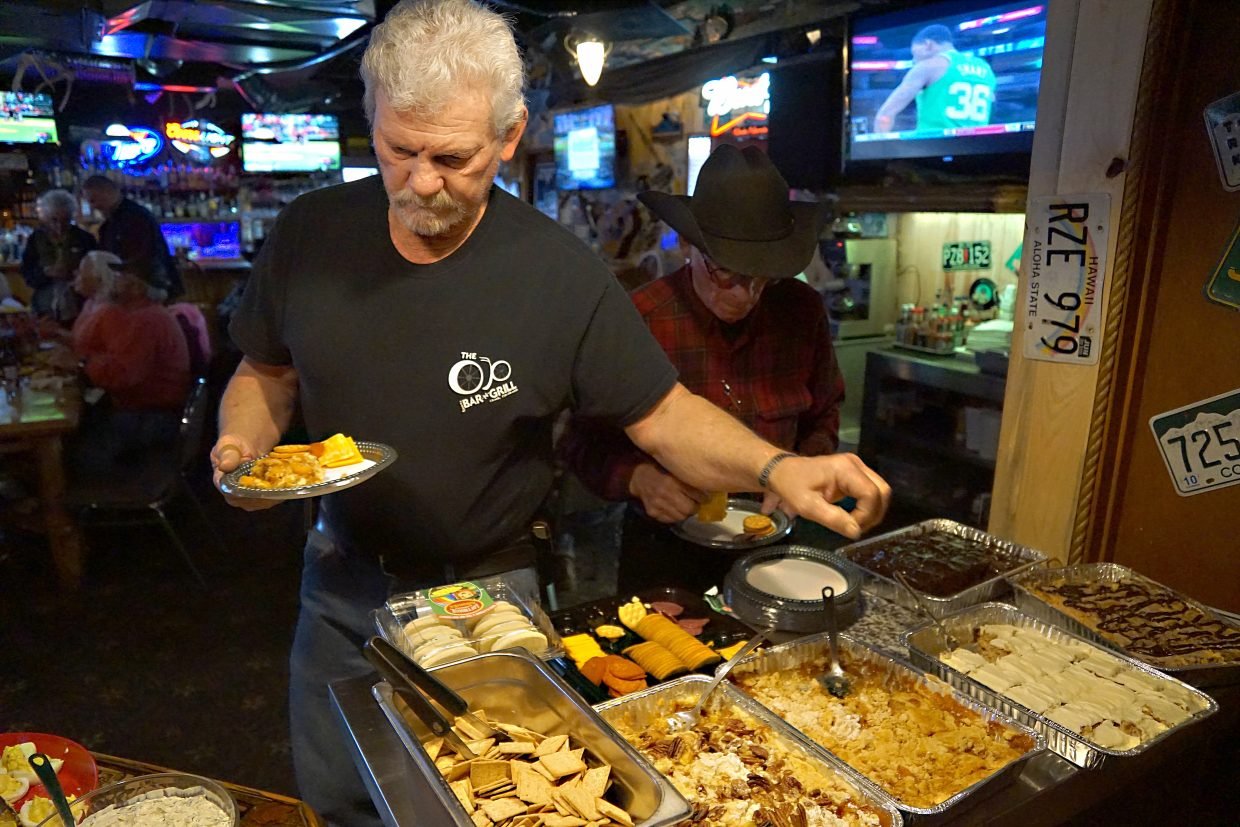 George Vassek fills his plate with some of the plentiful food offered at the OP Bar & Grill in Craig for those who came out to wish the Ann and George Kidder well as they prepare to leave Moffat County.