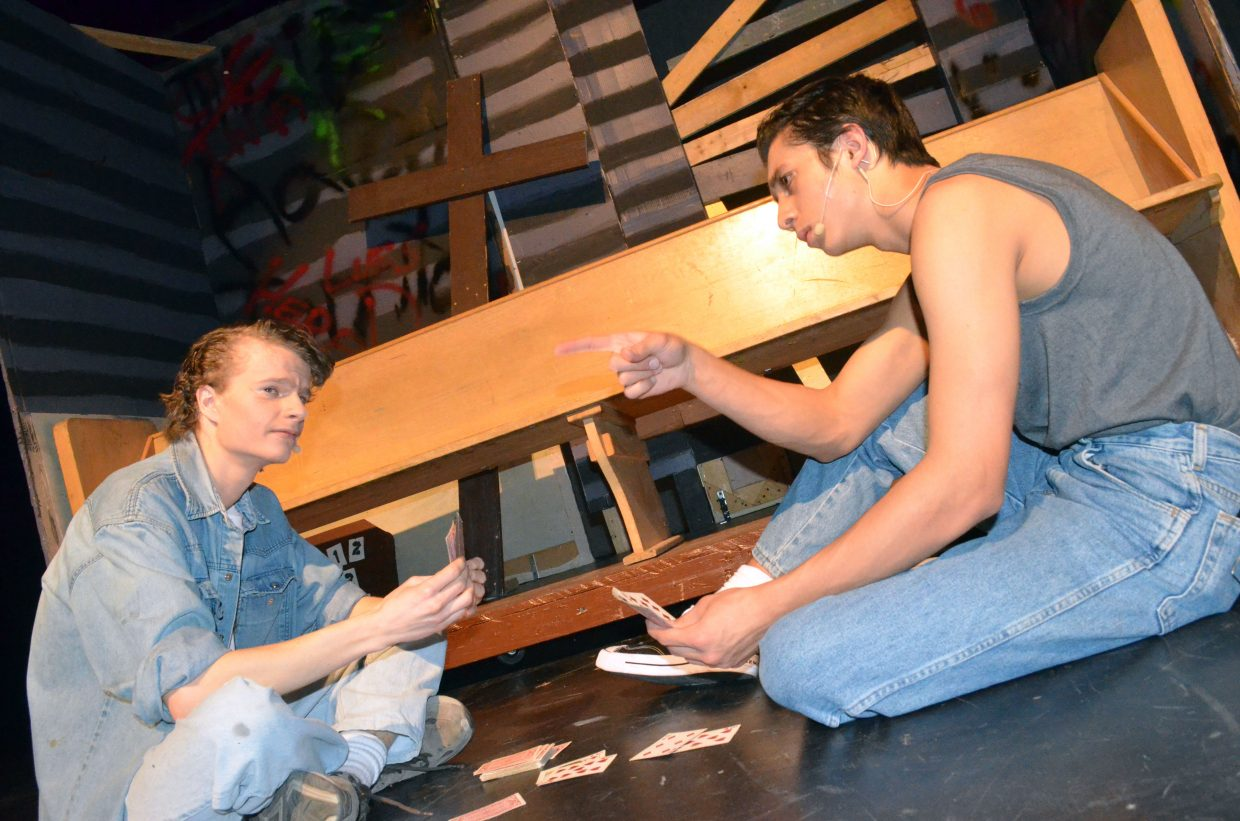 Johnny and Ponyboy (Jeremy Looper, Sambu Shrestha) pass time playing cards while in hiding.