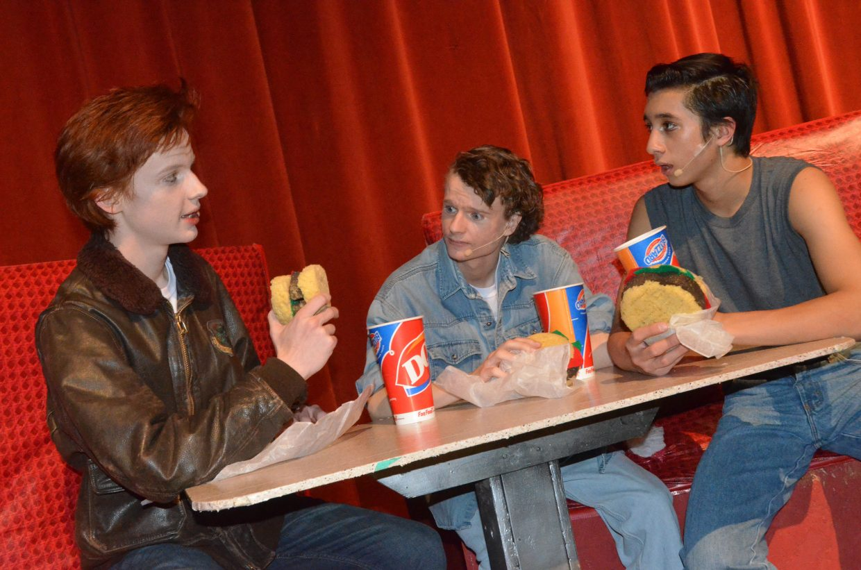From left, Dally (Aaron Hill), Johnny (Jeremy Looper) and Ponyboy (Sambu Shrestha) share a meal in