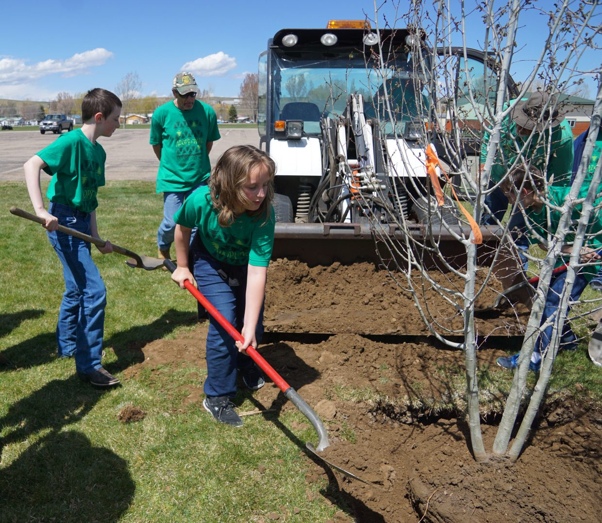 Students help City Parks and Recreation staff shovel dirt while planting a new clump of aspen trees at Woodbury Park, Monday, April 23.