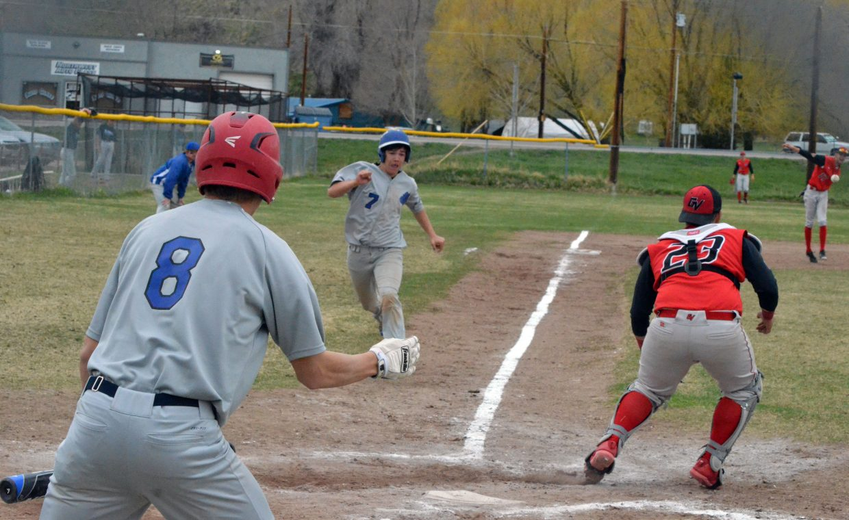 Moffat County High School's Hunter Smilanich waves home teammate Greg Hixson for one of many runs scored during the Bulldogs' Thursday game against Grand Valley. MCHS won 15-1 in five innings.