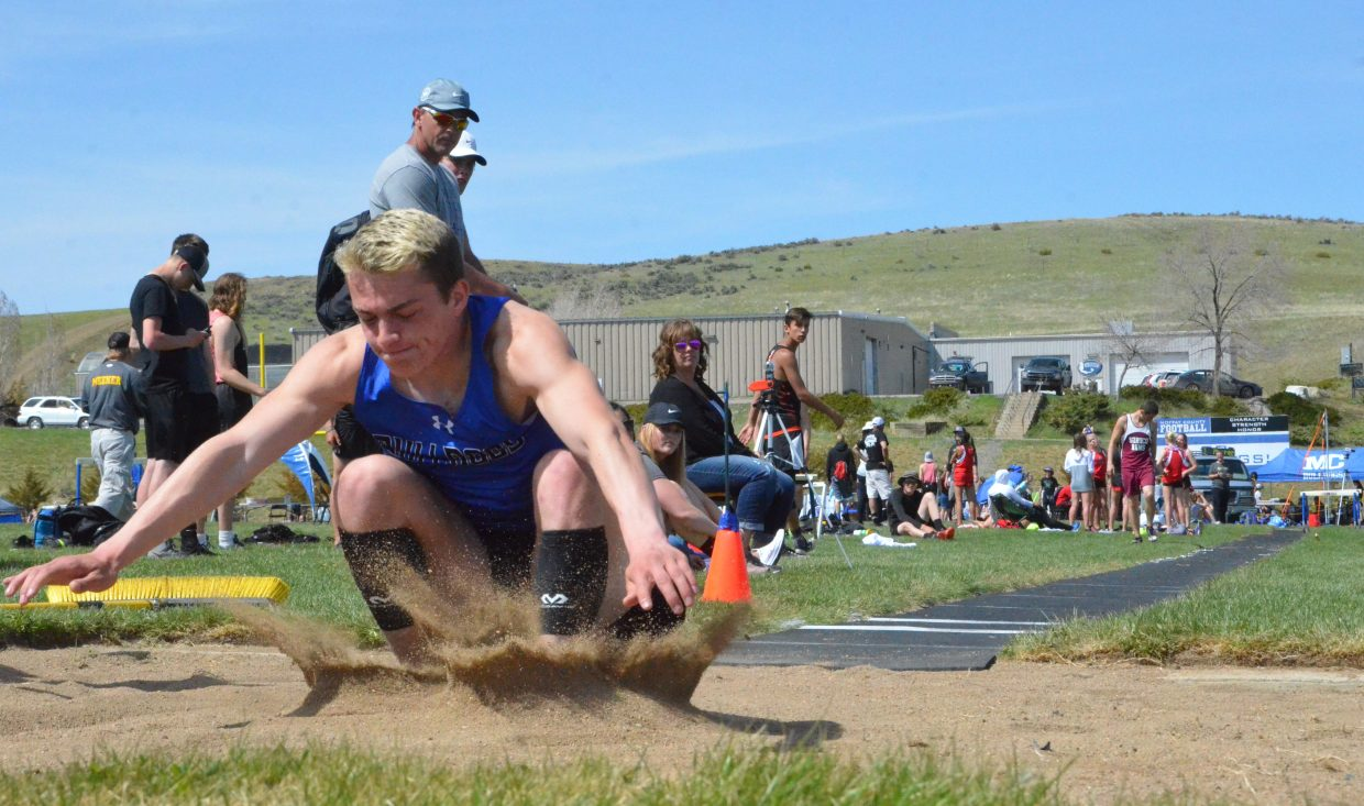 Moffat County High School's Jared Atkin kicks up a wave of sand in the boys long jump pit Friday at the Clint Wells Invitational.
