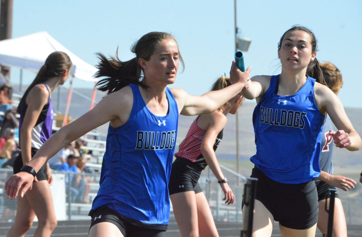 Moffat County High School's Josie Timmer, left, takes the handoff from teammate Abby Bohne during the girls 4x400-meter relay Friday at the Clint Wells Invitational. MCHS girls and boys teams each won the overall event.