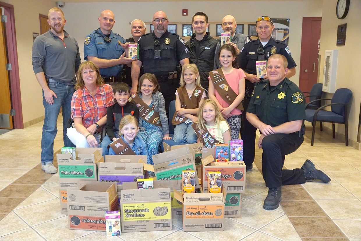 Law enforcement officers and local Girl Scouts pose with a massive stack of 140 boxes of cookies donated by the community.  Pictured, front row, from left,are Girl Scouts Audrey Laehr and Madison Doolin; middle row, Undersheriff Charlene Abdella, Joshua Kawchack, Xya McMahon, Josie Terry, Haley Duran and Sheriff KC Hume; back row, Officer Grant Laehr, Officer Ryan Hess, Police Chief Jerry Delong, Sergeant Anthony Fandel, Officer Josh Lyons, Captain Bill Leonard and Officer Bryan Gonzales.