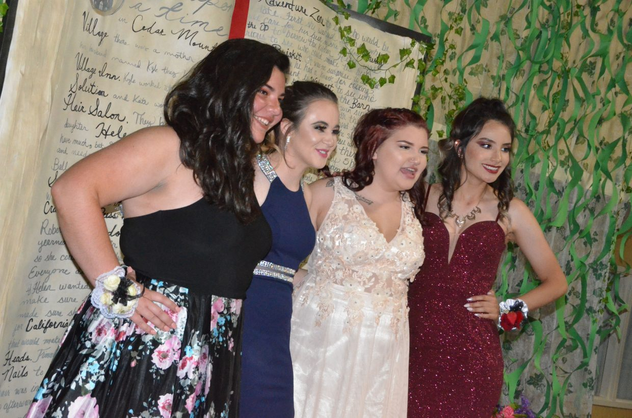 From left, Hali Reyes, Alyssa Zimmerman, Lilli Pierce and Lizbeth Magallanes pose onstage during Moffat County High School prom at Clarion Inn & Suites.