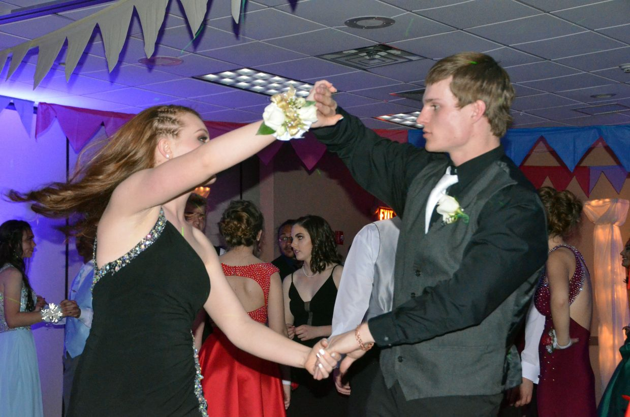 Rylie Anderson, left, and Drake Zimmerman twirl around the dance floor during Moffat County High School prom at Clarion Inn & Suites.