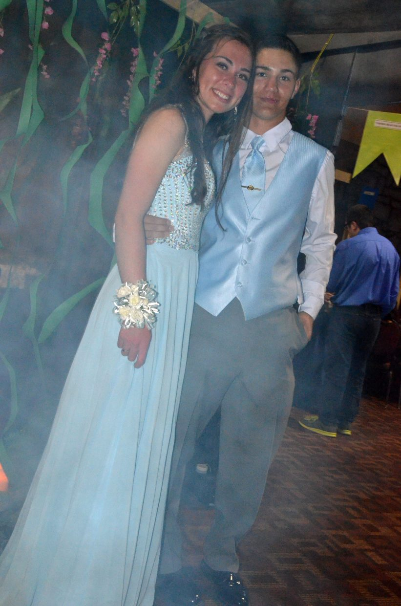 Abby Bohne, left, and Greg Hixson let the mist from a fog machine swirl around them during Moffat County High School prom at Clarion Inn & Suites.