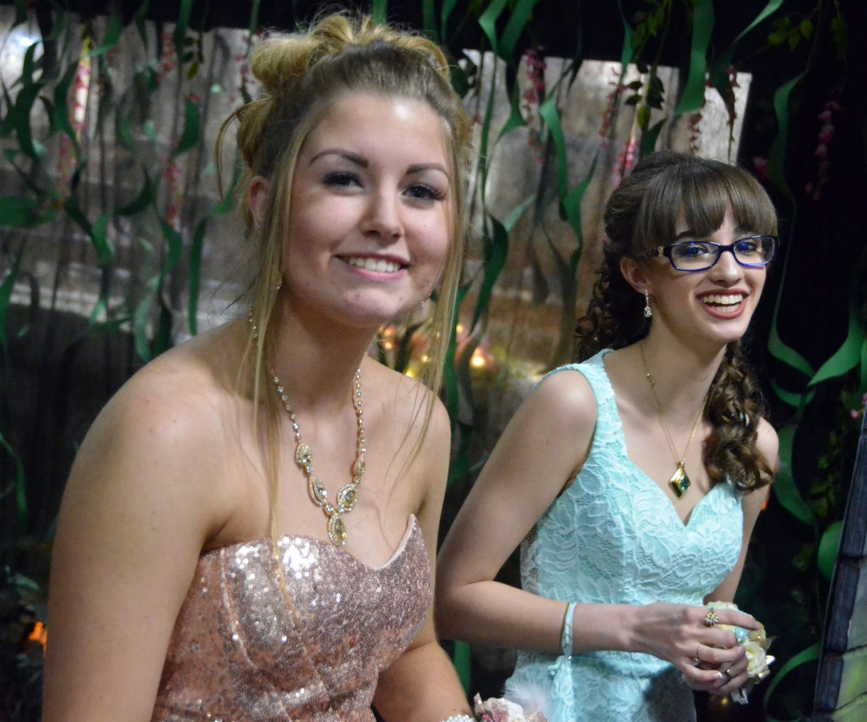 Bella Green, left, and Abigail Hall enter the Moffat County High School prom at Clarion Inn & Suites.