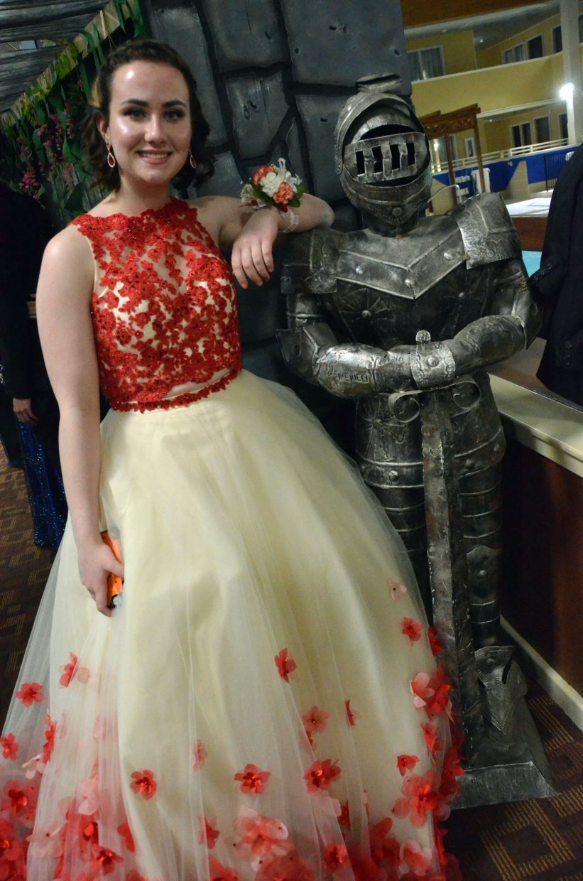 Courtney Smith leans on a suit of armor standing guard during Moffat County High School prom at Clarion Inn & Suites.