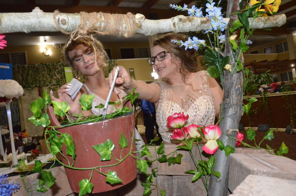 Madelaine Petersen, left, and Kaylee Hahn cast their votes for royalty during Moffat County High School prom at Clarion Inn & Suites.