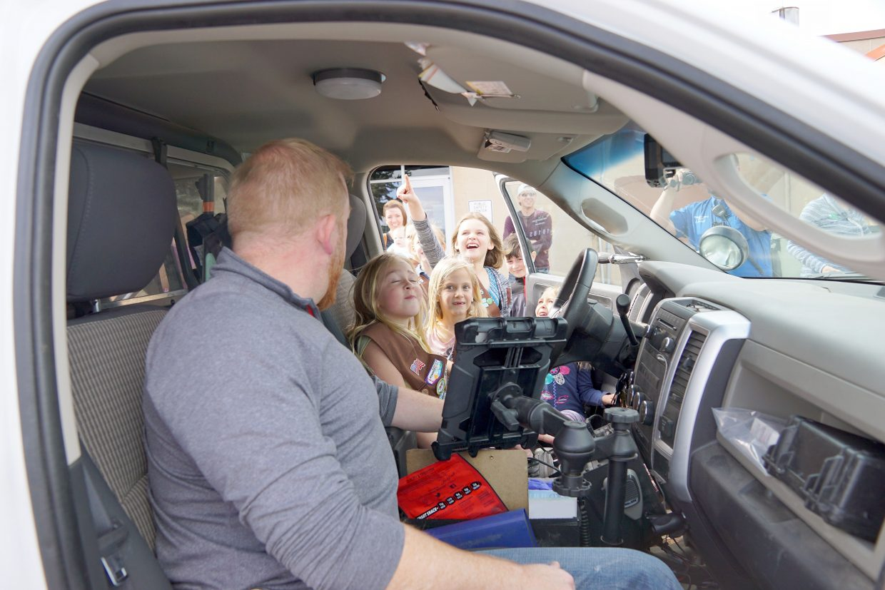 Officer Grant Laehr shows local Girl Scouts some of the gadgets in a Craig Police Department truck and how to activate one of the sirens.