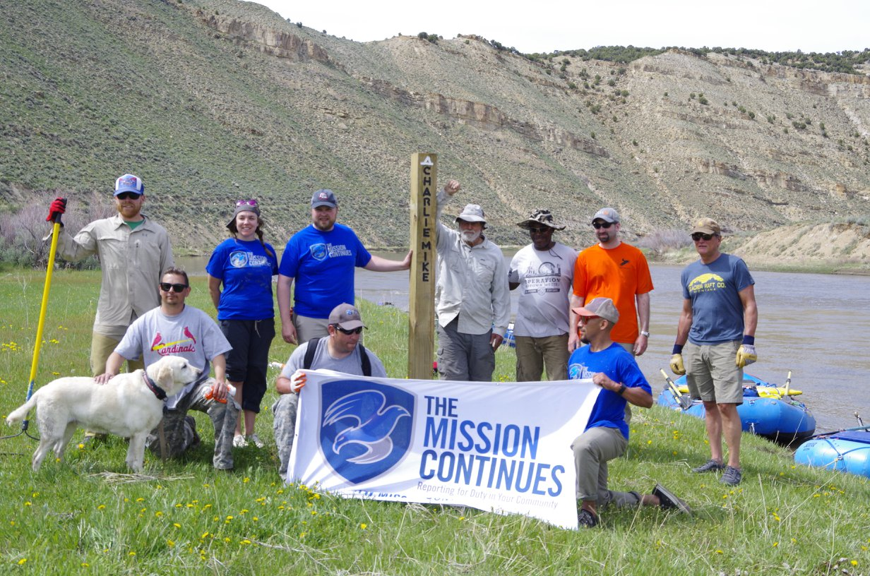 Volunteers gather at one of the new camp marker posts.
