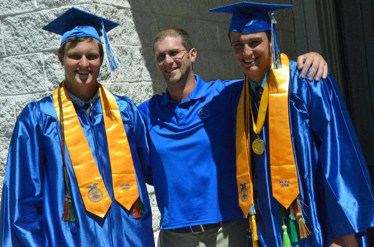 Moffat County High School graduates Toryn Hume and Colby Beckett join athletic trainer Marshall Kraker after Saturday's graduation ceremony.