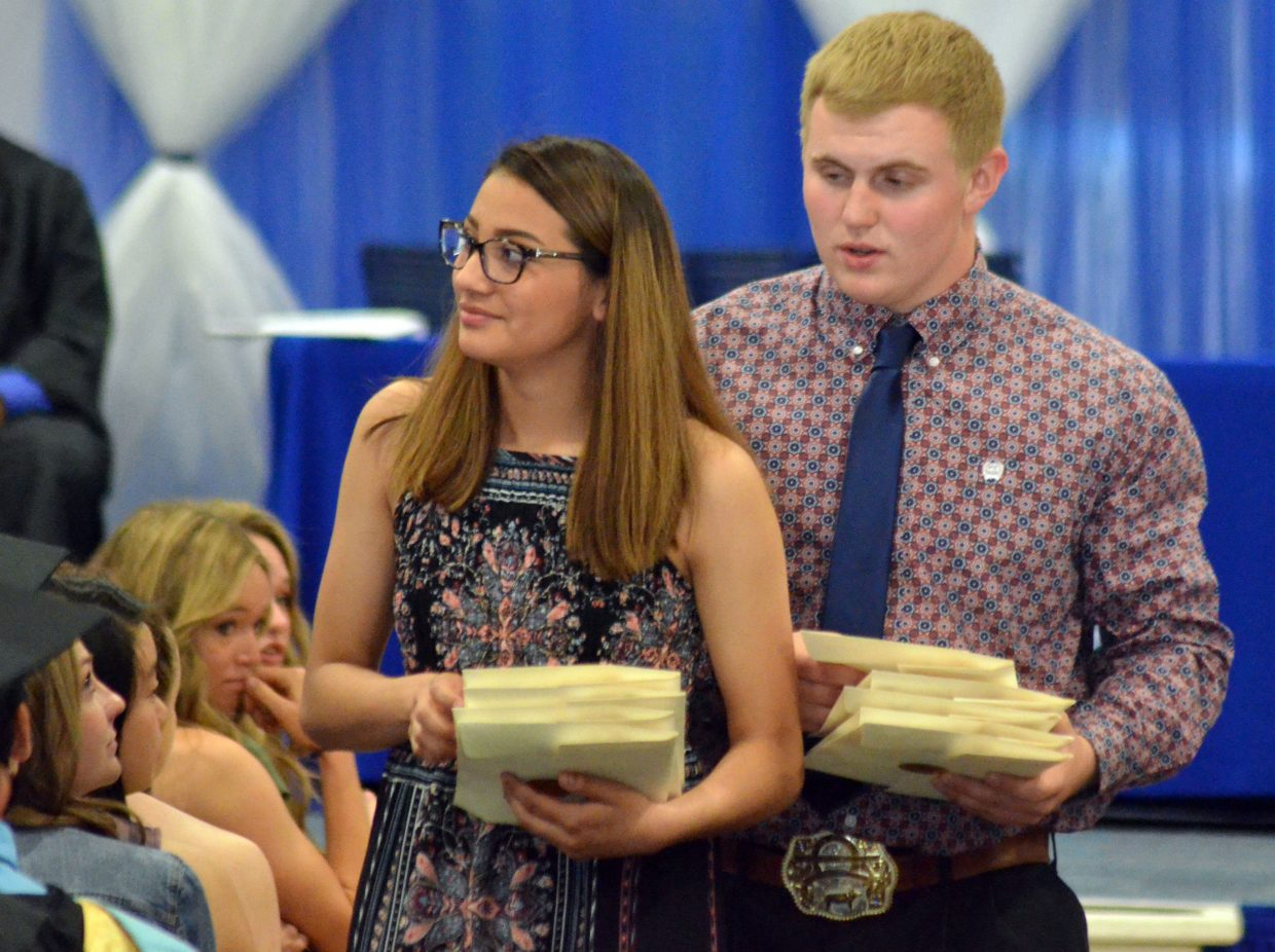 Moffat County High School junior class escorts Alyssa Chavez and Jared Baker pass out scholarship packages during Saturday's graduation ceremony.