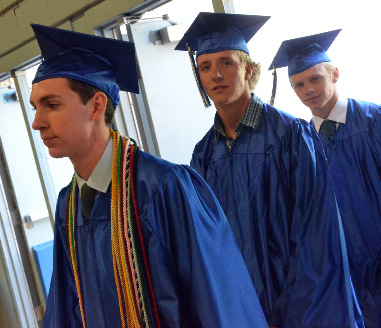 Moffat County High School's Grant Wade, Tristen Walls and Adain Wilmot bring up the rear entering the gym during Saturday's graduation ceremony.