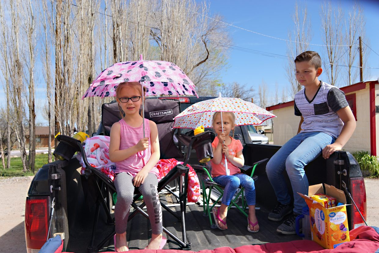 Children patiently wait for more than 460 horses to trot through the town of Maybell.