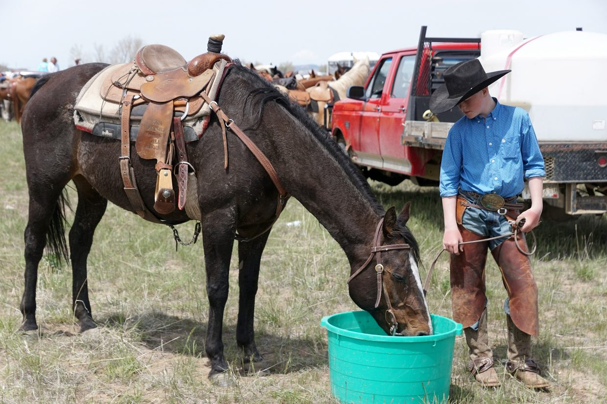 A young cowboy looks after his horse before grabbing a bite of lunch.