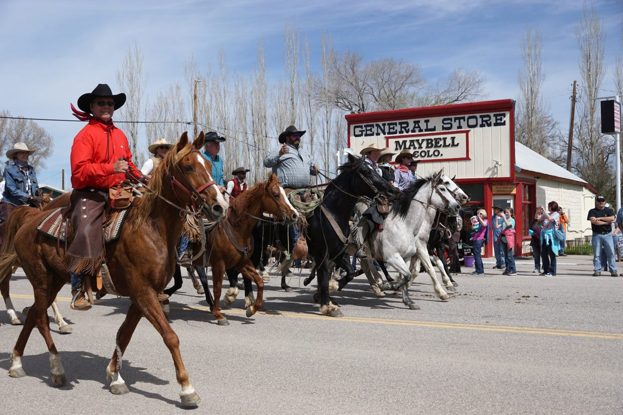 Some of the approximately 30 paying riders and another 30 experienced riders make their way through Maybell.