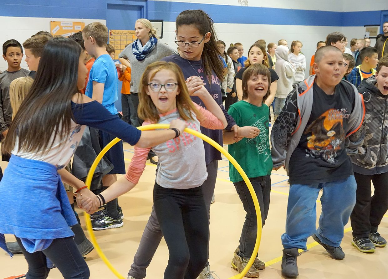 Students work together to pass a hula-hoop in one of the many games at the Passport to Reading awards barbecue.