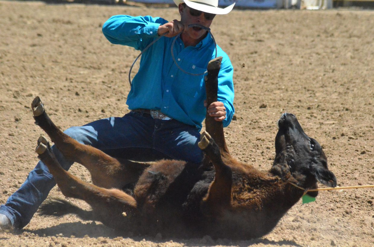 Yampa's Jace Logan wrestles a calf into submission to win the tie down roping Friday at Colorado State High School Rodeo Association State Finals at Moffat County Fairgrounds.