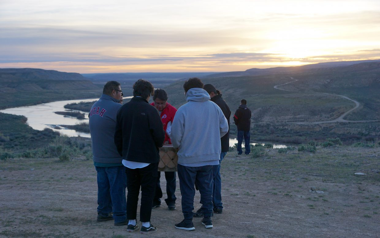 Elder Rafael Knip, far right, offers prayers to the sun and tobacco leaf to the earth, while family members Serenus Knip, Bart and Red Heart Powaukee, Leroy Cesspooch, Eagle Manning, Kyrie Duncan and Isaac Sarawop drum and sing.