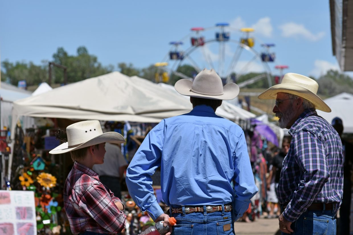 From left, Dorian Hotchkiss, Michael Foth and Tom Moulden look over the crowd at the Old West Festival Arts and Crafts Show on Saturday, part of the Grand Old West Days in Craig. The trio had a booth at the show to advertise their Open Range Rodeo Bible Camp.