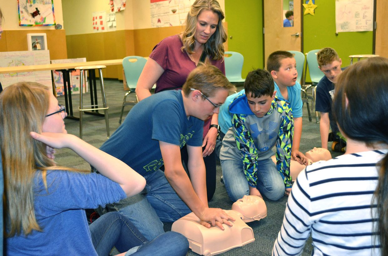 CMS seventh-grade teacher Amy Peck helps students Tristan Malvitz, left, and Christian Morales as they practice CPR techniques during Trauma Day, held Friday, May 11 at CMS.