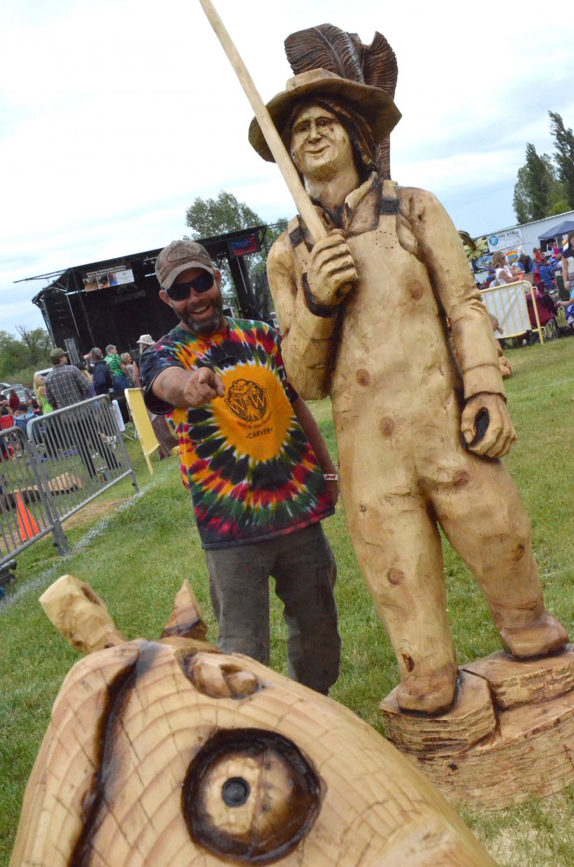 Matt Ounsworth of Fort Collins cheers on his wooden fisherman in catching a cod in the carving