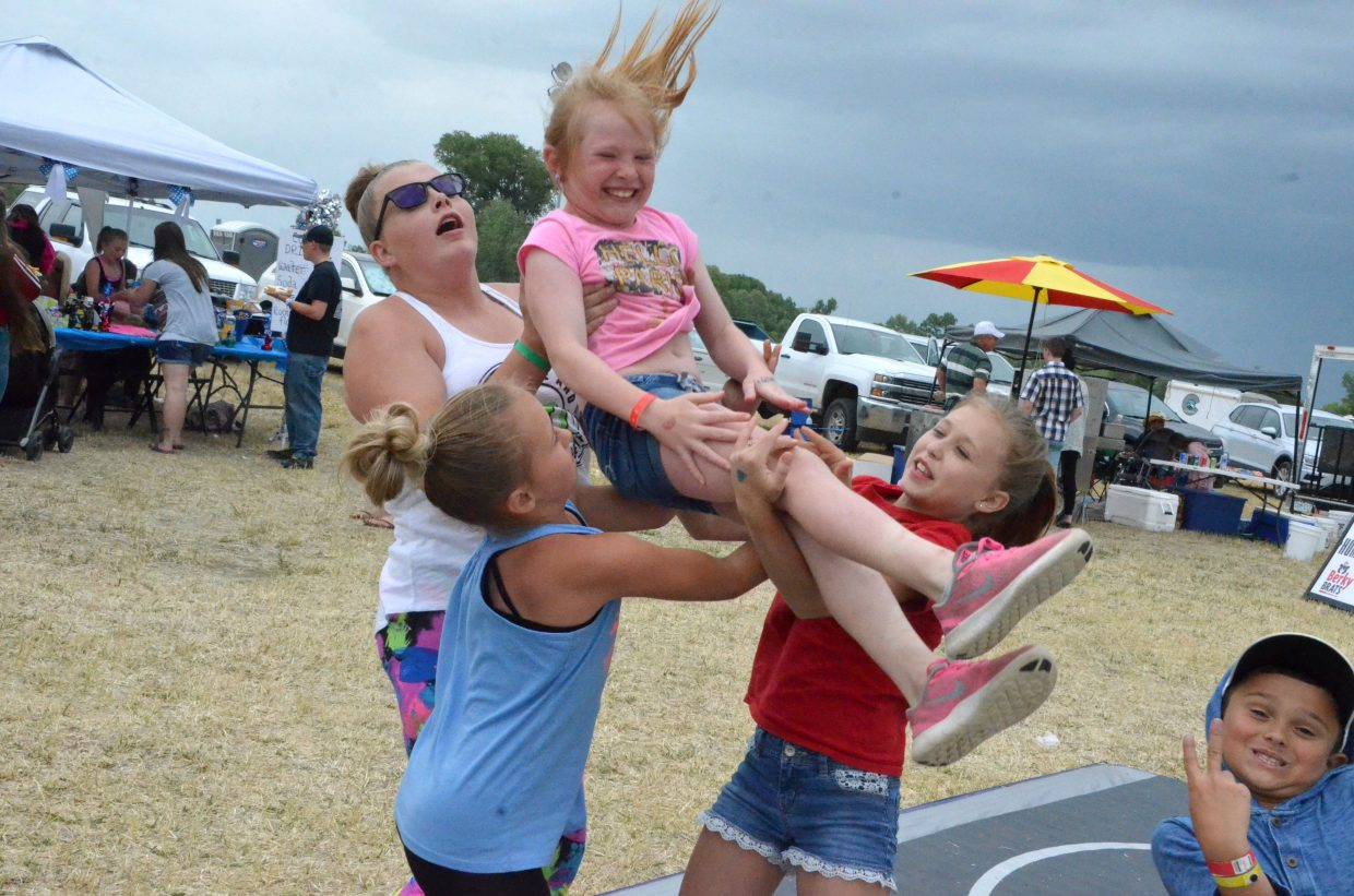 Members of Moffat County Elite Cheer perform a basket toss while taking a break from duty at the team's food booth Saturday during the 19th annual Whittle the Wood Rendezvous.