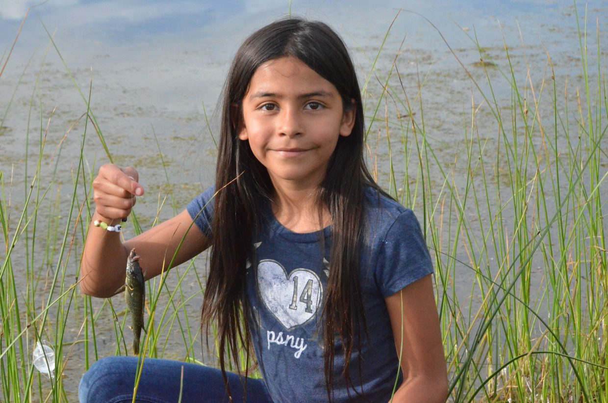 Marissa Rodriguez holds up her fish before tossing it back in the waters of Little Rascals Pond during Cops, Kids and Vets Fishing Day.